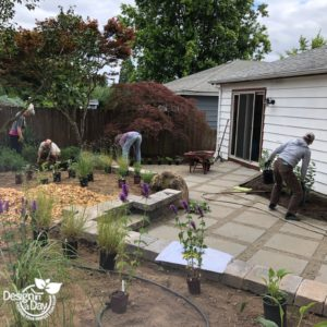 Planting crew installs pollinator garden design in Roseway neighborhood backyard